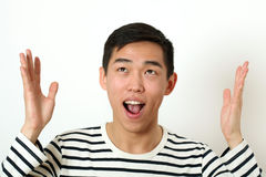 Funny young Asian man gesturing with his hand and looking upward Royalty Free Stock Photography