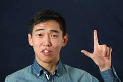 Funny young Asian man giving number two hand sign Stock Images