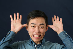 Funny young Asian man making face Royalty Free Stock Photography