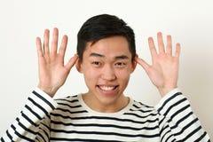 Funny young Asian man making face and looking at camera Royalty Free Stock Photos