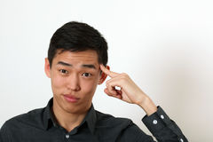 Funny young Asian man pointing his index finger against his temp Stock Photos