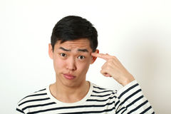 Funny young Asian man pointing his index finger against his temp Royalty Free Stock Photo