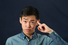 Funny young Asian man pointing his index finger Stock Photo
