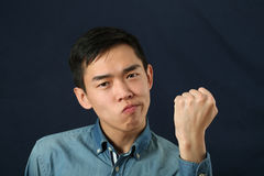 Funny young Asian man shaking his fist. And looking at camera Royalty Free Stock Photography