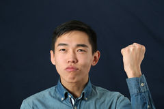 Funny young Asian man shaking his fist and looking upward Stock Image