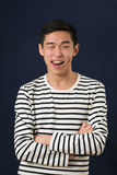 Funny young Asian man showing his tongue Royalty Free Stock Photography