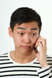 Funny young Asian man using a smartphone Royalty Free Stock Photo
