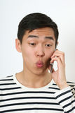 Funny young Asian man using a smartphone Royalty Free Stock Photos