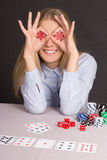 Funny young attractive woman playing poker over grey Royalty Free Stock Photos