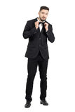 Funny young bearded man adjusting bow tie looking at camera Stock Photos