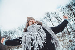 Funny young bearded man in the winter in nature. The man raised his hands up rejoices winter Stock Images