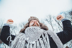 Funny young bearded man in the winter in nature. The man raised his hands up rejoices winter Royalty Free Stock Images