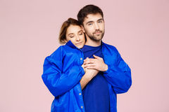 Funny young beautiful couple wearing one jacket embracing smiling over light pink background. Royalty Free Stock Image