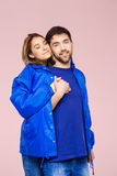 Funny young beautiful couple wearing one jacket embracing smiling over light pink background. Stock Photos