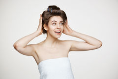 Funny young beautiful girl in hair curlers and towel posing over white background. Beauty cosmetology and spa. Royalty Free Stock Photos