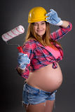 Funny young beautiful pregnant woman in builder's helmet with  p Royalty Free Stock Photography