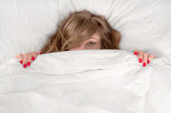 Funny young beautiful woman lying in bed under blanket. Woman hiding under blanket on bed at bedroom Royalty Free Stock Photo