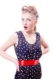 Funny young blond pinup woman in polka dot dress with curlers wonderingly akimbo looking at camera on white Royalty Free Stock Image