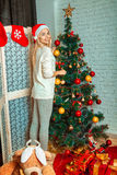 Funny young blonde girl decorates a christmas tree in santa hat Royalty Free Stock Photo