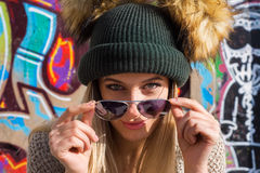 Funny young blonde woman in hat and sunglasses looking at camera Stock Photography