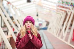 Funny young blonde woman in red knitted hat posing with candy ca Royalty Free Stock Photo