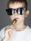 Funny Young Boy Eating A Lollipop.Fashionable child in sunglasses. Fashion portrait of Funny Young Boy Eating A Lollipop.Fashionable child in sunglasses Royalty Free Stock Photo