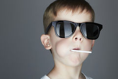 Funny Young Boy Eating A Lollipop.Fashionable child in sunglasses. Fashion portrait of Funny Young Boy Eating A Lollipop.Fashionable child in sunglasses Stock Photos