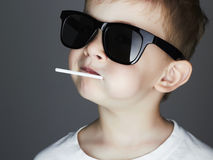 Funny Young Boy with A Lollipop.Fashionable child in sunglasses Royalty Free Stock Photography