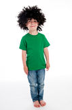 Funny Young Boy Wearing a big Black Wig. Full length young smiling boy standing in studio on white background with a big black funny wig Royalty Free Stock Photos