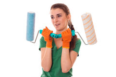 Funny young brunette builder girl in uniform makes renovation with paint rollers in her hands isolated on white Royalty Free Stock Photo
