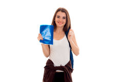 Funny young brunette student with backpack and books in her hands posing on camera isolated on white background Royalty Free Stock Photos