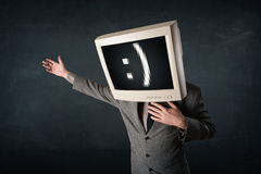 Funny young businessman with a monitor on his head and smiley on Stock Photos