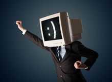 Funny young businessman with a monitor on his head and smiley on Stock Image