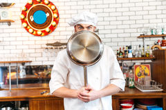 Funny young chef cook covered his face with frying pan. On the kitchen Stock Photography