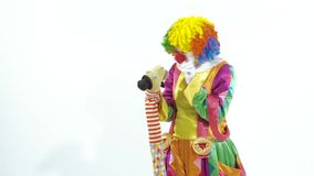 Funny young clown playing with puppet stock footage