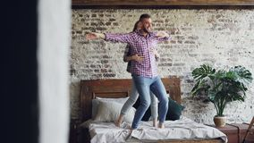 Funny young couple is dancing on bed having fun in loft style bedroom and laughing. Happy people, modern lifestyle and stock footage