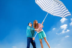 Funny and young couple have fun with beach umbrella on blue sky Stock Image
