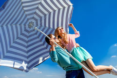 Funny and young couple have fun with beach umbrella on the roof. On blue sky background Stock Photo