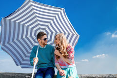 Funny and young couple have fun with beach umbrella on the roof Royalty Free Stock Image