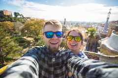 Funny young couple looking at camera taking photo with smart phone smiling in Park Guell, Barcelona, Spain. royalty free stock photos
