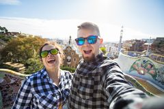 Funny young couple looking at camera taking photo with smart phone smiling in Park Guell, Barcelona, Spain. Funny young couple looking at camera taking photo stock photos