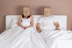 Funny young couple with paper bags over heads Stock Photography