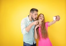 Funny young couple taking selfie on background. Funny young couple taking selfie on color background royalty free stock photos