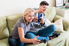 Funny young couple playing together a video game on console. Funny young couple wearing casual clothes while playing together a video game on console at home royalty free stock photo