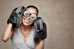 Funny crazy woman with big eyes, glasses and boxing gloves. Funny young crazy woman wearing plastic fun big glasses that makes the eyes look very big and boxing stock photo