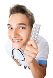 Funny young doctor holding pills Stock Image