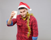 Funny young drunk man wearing Santa hat holding a paper cup Stock Image