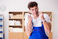 The funny young electrician tangled in cables. Funny young electrician tangled in cables Royalty Free Stock Images