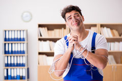 The funny young electrician tangled in cables. Funny young electrician tangled in cables Royalty Free Stock Image