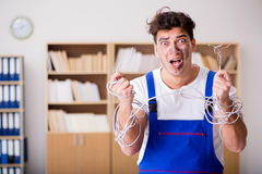 The funny young electrician tangled in cables Stock Image